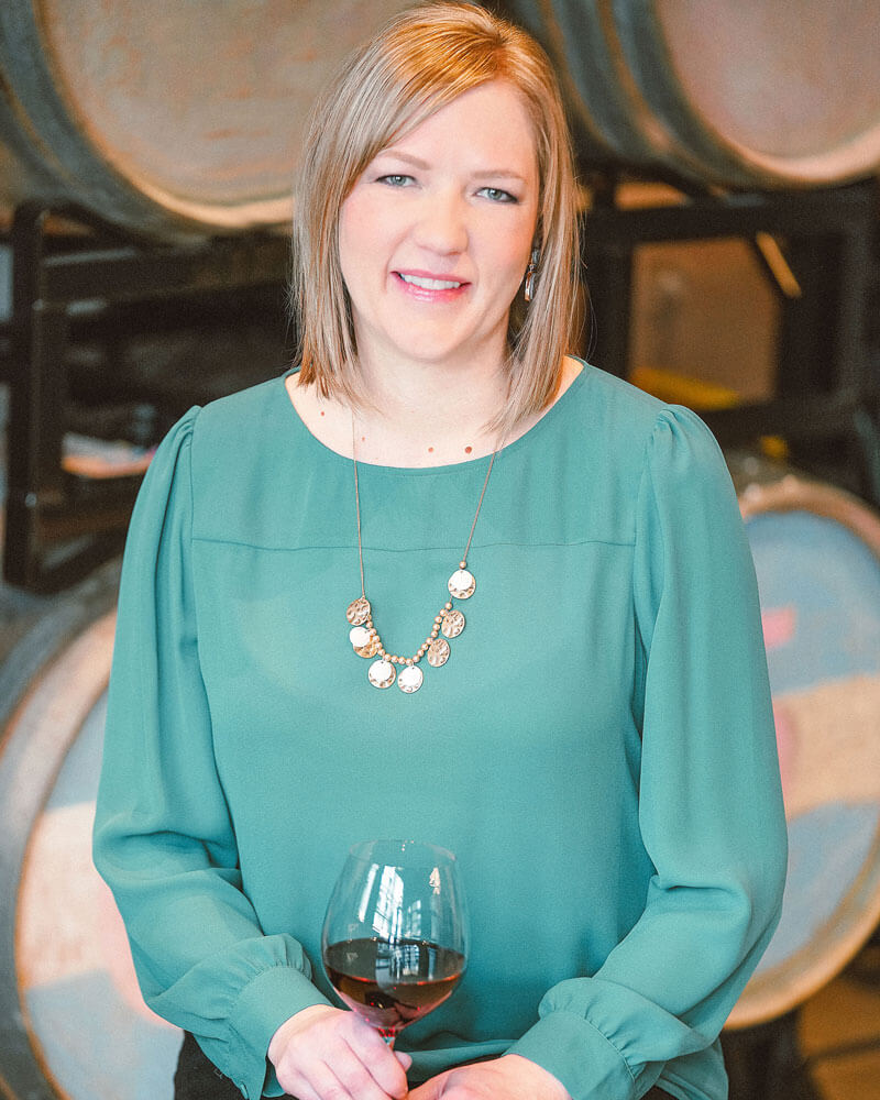 Christina Mao standing in front of wine barrels holding a glass of wine